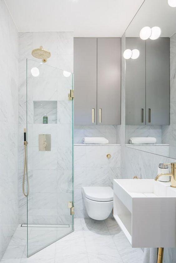 mała łazienka powiększona optycznie jasnymi ścianami, meblami na połysk u dużą ilością luster