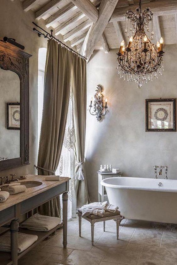 łazienka w stylu francuskim z mięsistymi zasłonami wolnostojącą na nóżkach wanną z pałacowymi kinkietami i ;bogatym żyrandolem w odcieniu beżu