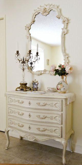 łazienka w stylu francuskim w odcieni bieli z dekoracyjnymi szafkami i przepięknym lustrem w w równie dekoracyjnej ramie