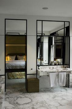 łazienka w stylu francuskim połączona z sypialnią widoczną w odbiciu pięknych luster