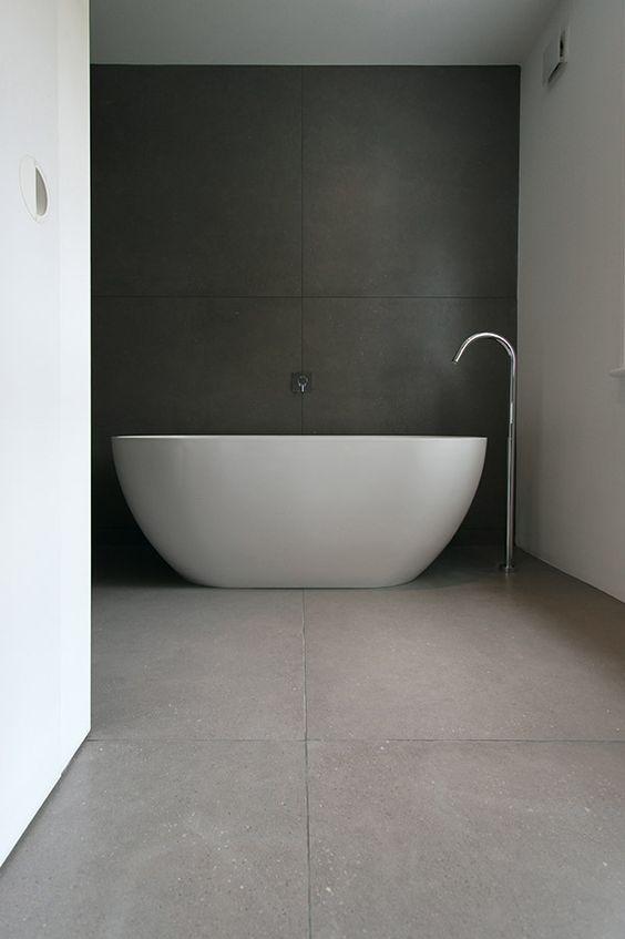 płytki wielkoformatowe w kolorze szarości zarówno na ścianach jak i podłodze w połączeniu z nowoczesną wolnostojącą białą wanną