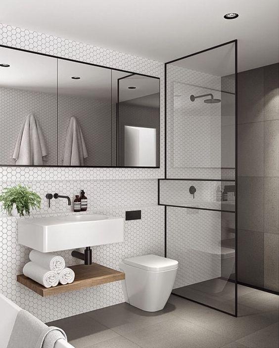 biała mała łazienka z prysznicem walk in oddzielonym szybą w czarnych ramach z dużym poziomym lustrem powiększającym optycznie powierzchnię
