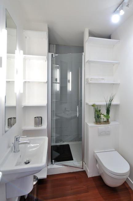 mała łazienka z kabiną prysznicową schowaną za ścianką z podwieszoną muszlą klozetową